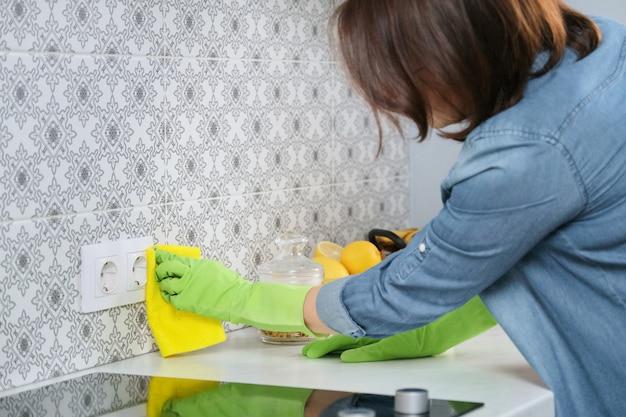 Vrouw in handschoenen met vodden schoonmakend huis in keuken Premium Foto