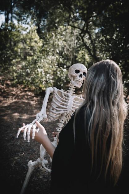 Vrouw in heksenkostuum buigend skelet Gratis Foto