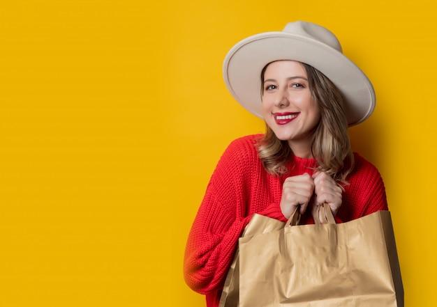 Vrouw in hoed en boodschappentassen Premium Foto