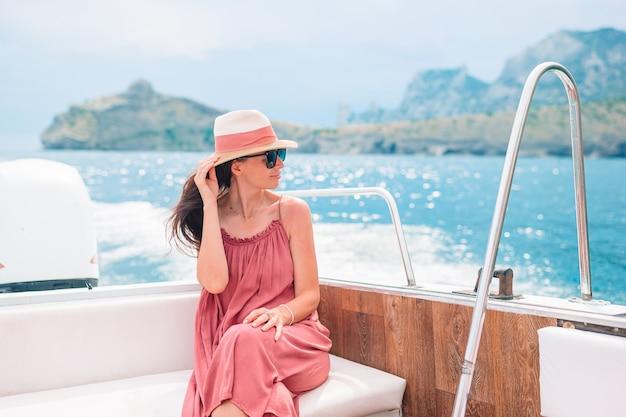 Vrouw in hoed en kleding die op boot in duidelijke open zee zeilen Premium Foto
