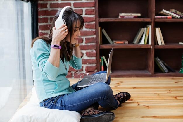 Vrouw in hoofdtelefoon werkt op een laptop Premium Foto