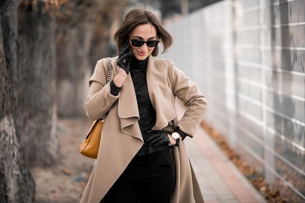 Vrouw in jas met telefoon Gratis Foto