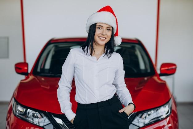 Vrouw in kerstmuts bij de rode auto in een autoshowroom Gratis Foto