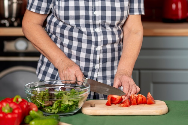 Vrouw in keuken kokende salade Gratis Foto
