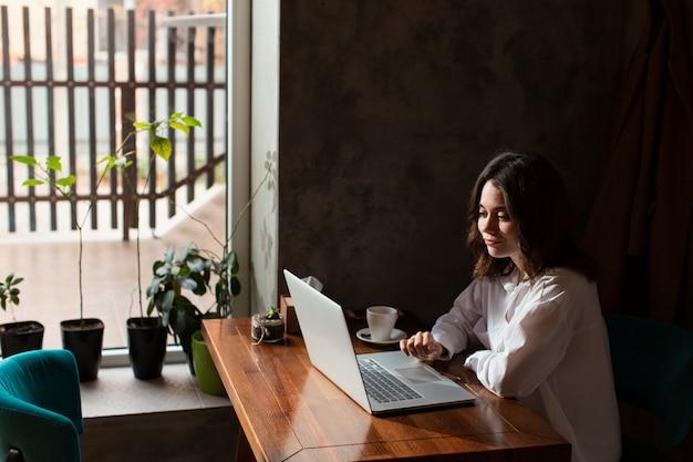 Vrouw in koffiewinkel die aan laptop werkt Gratis Foto