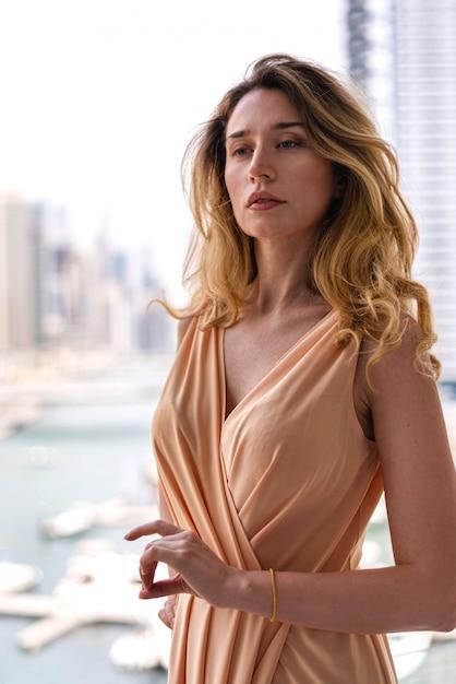 Vrouw in lange jurk in dubai marina Premium Foto