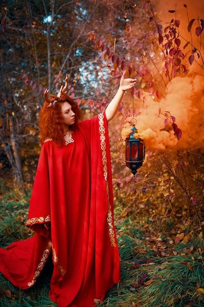 Vrouw in lange rode kleding met hertenhoornen in de herfstbos. Premium Foto