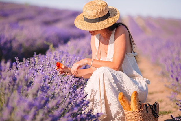 Vrouw in lavendel bloemen veld bij zonsondergang in witte jurk en hoed Premium Foto