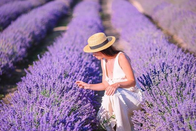 Vrouw in lavendel bloemen veld in witte jurk en hoed Premium Foto