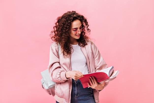 Vrouw in lichte outfit leest notities in notitieboekje op roze achtergrond Gratis Foto