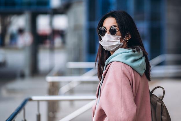 Vrouw in medische masker buiten in de lege stad. bescherming van de gezondheid en preventie van virusuitbraak, coronavirus, covid-19, epidemie, pandemie, infectieziekten, quarantaineconcept. Premium Foto