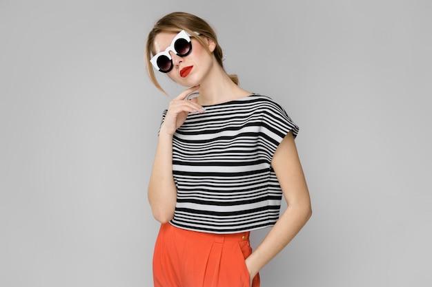 Vrouw in modieuze kleding en zonnebril Premium Foto