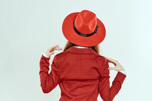 Vrouw in rode hoed en jasje achteraanzicht elegante stijl lichte achtergrond Premium Foto