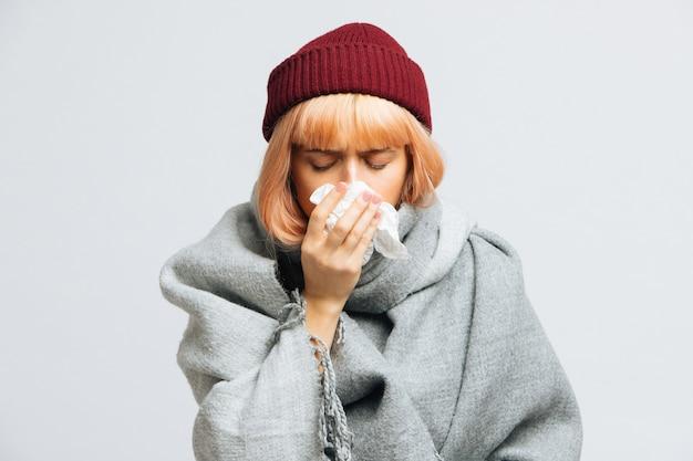 Vrouw in rode hoed, warme sjaal met papieren servet niest, ervaart allergiesymptomen, verkouden Premium Foto