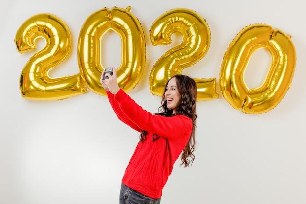 Vrouw in rode sweater die foto's met uitstekende camera voor 2020 nieuwe jaarballons nemen Premium Foto