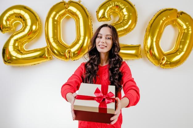 Vrouw in rode sweater openingskerstmis huidig voor 2020 nieuwe jaarballons Premium Foto