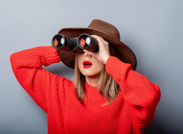 Vrouw in rode trui en hoed met verrekijker Premium Foto