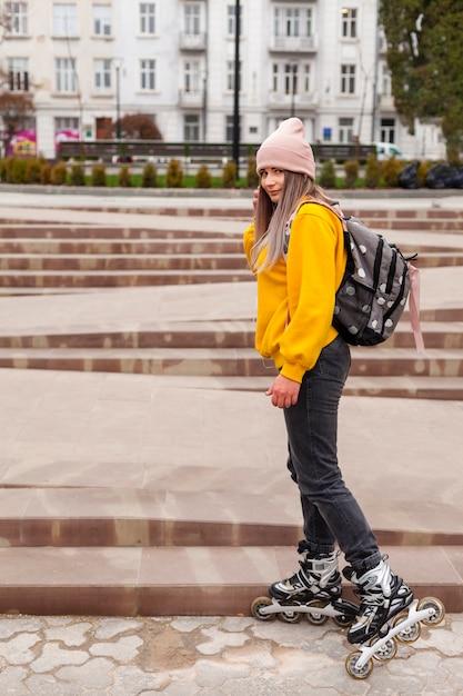 Vrouw in rolbladen die in de stad stellen Gratis Foto