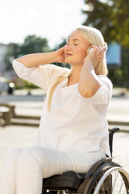 Vrouw in rolstoel genieten van muziek op koptelefoon buiten Gratis Foto