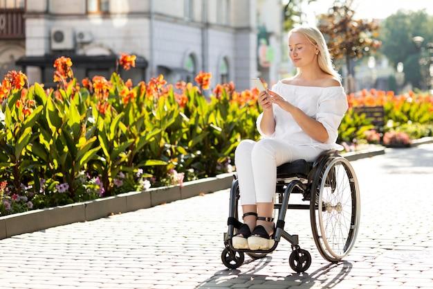 Vrouw in rolstoel in de stad die smartphone met exemplaarruimte gebruikt Gratis Foto