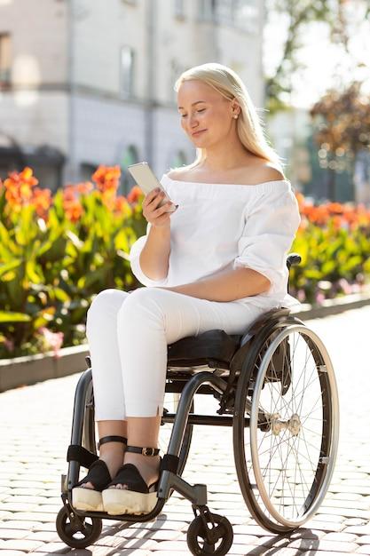 Vrouw in rolstoel in de stad met smartphone Premium Foto