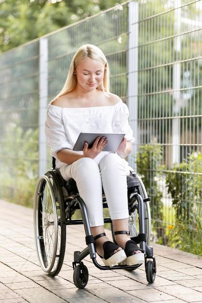 Vrouw in rolstoel met behulp van tablet Gratis Foto