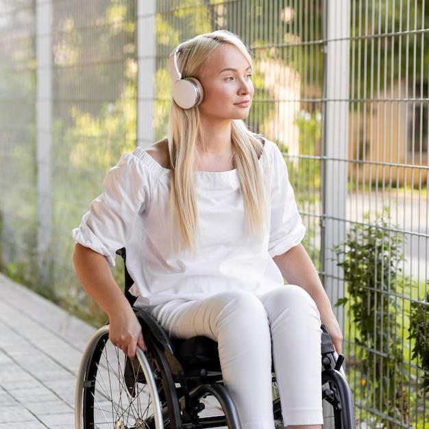 Vrouw in rolstoel met koptelefoon buiten Gratis Foto