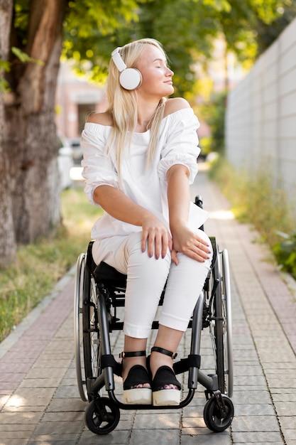 Vrouw in rolstoel met koptelefoon Gratis Foto