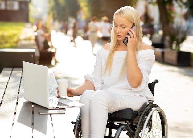 Vrouw in rolstoel met laptop buitenshuis en praten aan de telefoon Premium Foto