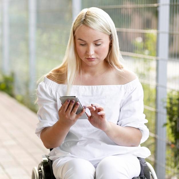 Vrouw in rolstoel met smartphone Gratis Foto