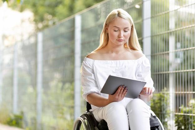 Vrouw in rolstoel met tablet Gratis Foto