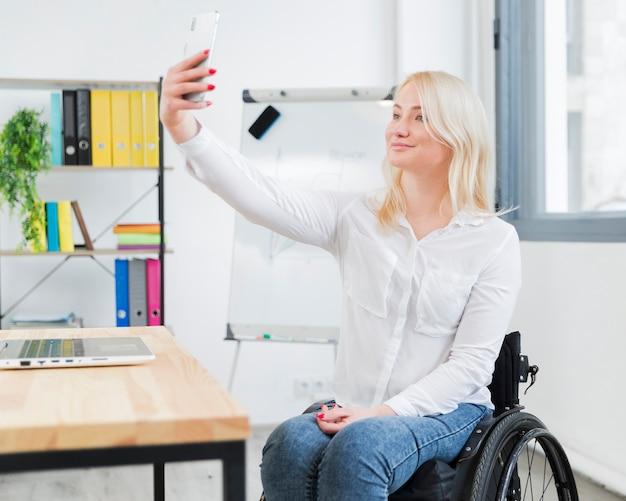 Vrouw in rolstoel nemen selfie op het werk Gratis Foto