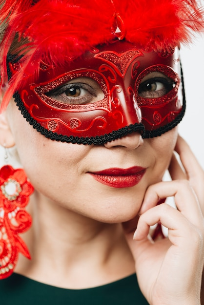 Vrouw in rood carnaval-masker met veer Gratis Foto