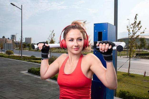Vrouw in rood met rode hoofdtelefoons die ina openbare ruimte van gymnastiektrainingen doen. Gratis Foto