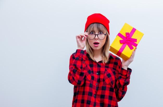Vrouw in rood shirt en hoed bedrijf vakantie geschenkdoos Premium Foto