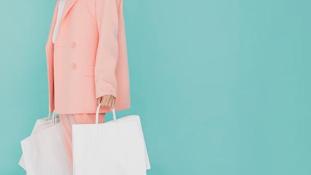 Vrouw in roze pak met winkelnetten Premium Foto
