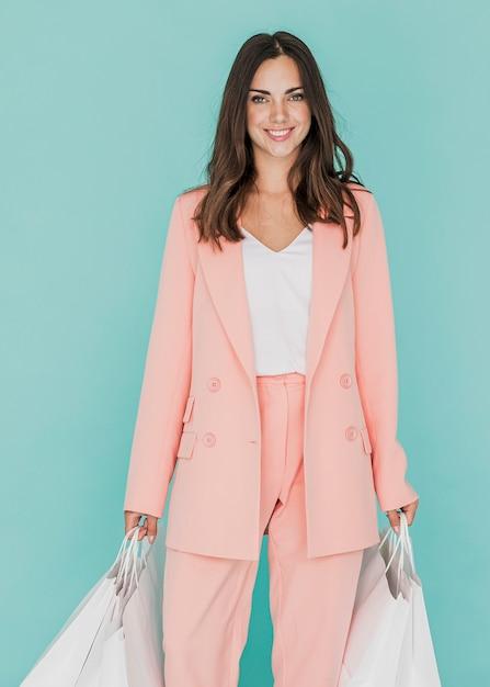 Vrouw in roze pak op blauwe achtergrond Gratis Foto