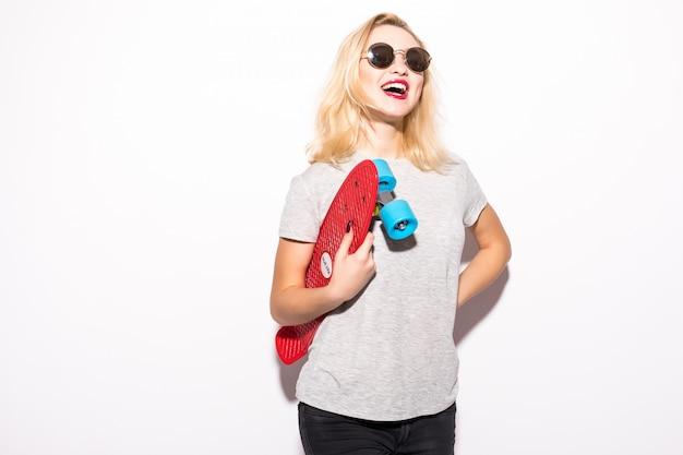 Vrouw in schitterende zonnebril met een skateboard in haar handen Gratis Foto