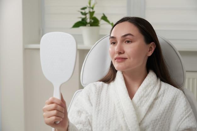 Vrouw in schoonheidssalon tevreden met resultaat van cosmetische procedure Premium Foto