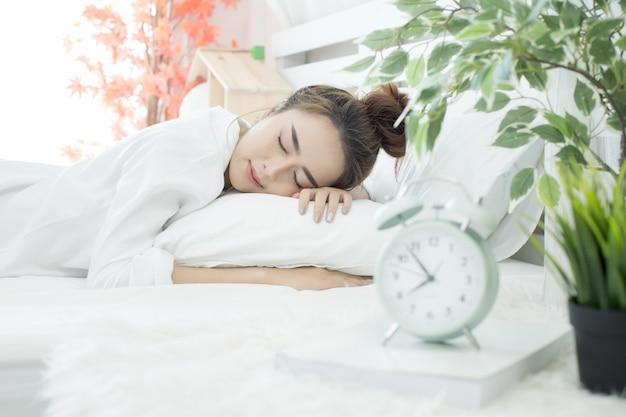 Vrouw in slaap in bed terwijl haar alarm de vroege tijd thuis in de slaapkamer laat zien Gratis Foto