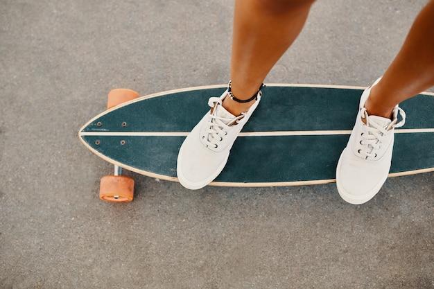 Vrouw in tennisschoenen die skateboard openlucht berijden op asfaltoppervlakte. Gratis Foto