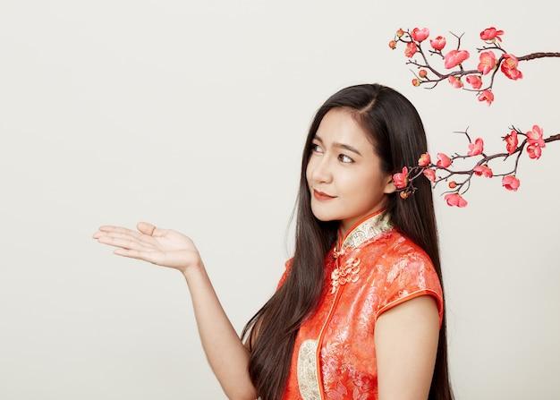 Vrouw in traditionele chinese rode kleding met pruimbloemen Premium Foto