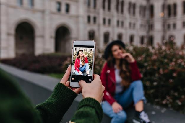 Vrouw in trendy groene trui nemen foto van haar zus naast zitten Gratis Foto