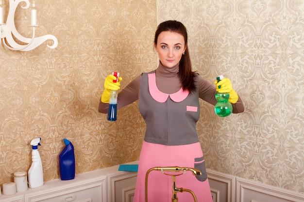 Vrouw in uniform en handschoenen met reinigingsmiddel Premium Foto
