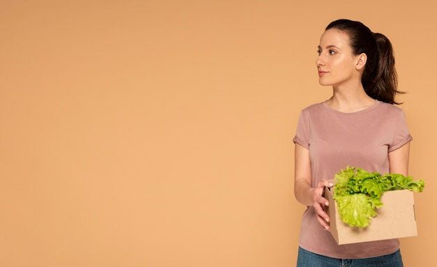 Vrouw in vrijetijdskleding met herbruikbare cartoon doos met groenten Gratis Foto