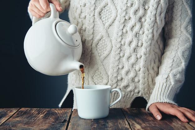 Vrouw in warme gebreide dikke trui giet zwarte thee uit grote witte theepot tot kopje op grunge houten tafel. vooraanzicht, anfa's, geen gezicht. Gratis Foto