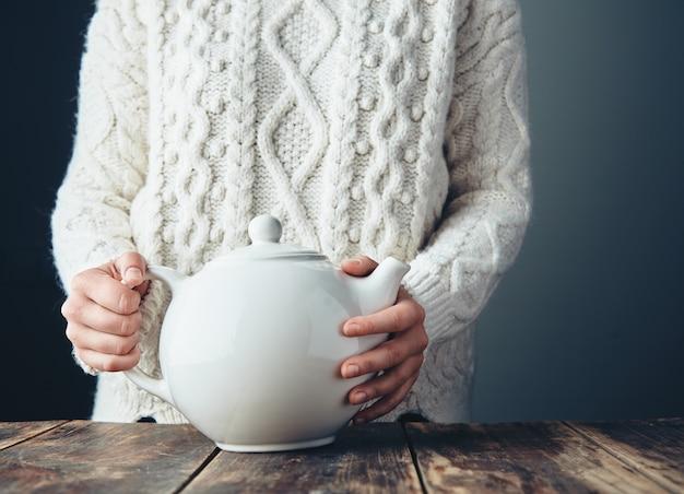 Vrouw in warme gebreide dikke trui houdt grote witte theepot met thee op grunge houten tafel. vooraanzicht, anfa's, geen gezicht. Gratis Foto