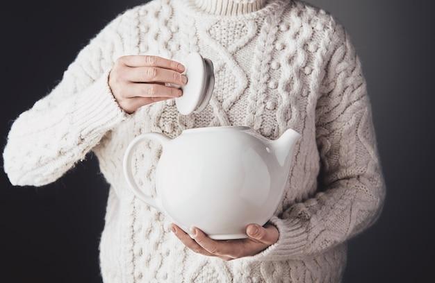 Vrouw in warme trui houdt aan de ene kant een grote witte keramische theepot vast en opent de dop met de andere Gratis Foto