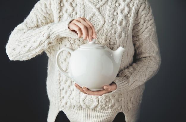 Vrouw in warme trui houdt grote witte theepot met thee in hartvorm. vooraanzicht, grunge houten tafel. anfas, geen gezicht. Gratis Foto