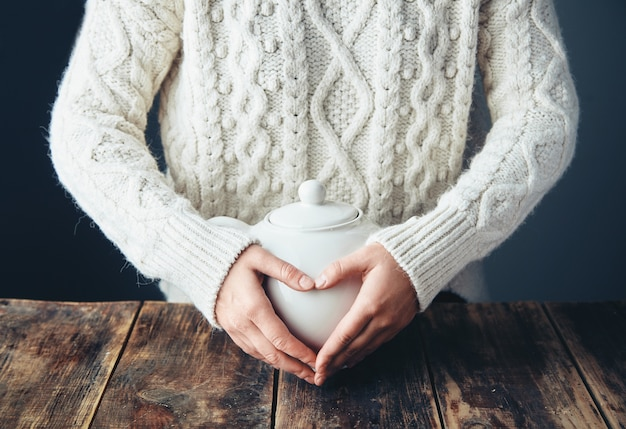 Vrouw in warme trui houdt handen op grote witte theepot met thee in hartvorm. vooraanzicht, grunge houten tafel. anfas, geen gezicht. Gratis Foto